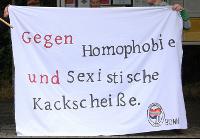 """Foto eines Transparents. Darauf steht in roter und schwarzer Schrift: """"Gegen Homophobie und sexistische Kackscheiße."""" Im unteren rechten Eck befindet sich das Logo der Antihomophoben Aktion Bonn."""